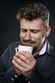 Man in admiration holds a cup of coffee in his hands and enjoying its smell.