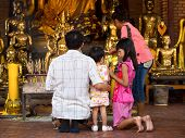 Asian Buddhist Family Making Offerings At Temple In Ayutthaya, Thailand
