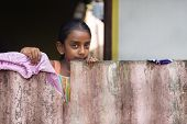 WELIGAMA, SRI LANKA - MARCH 8, 2014: Local girl behind wooden fence. Local people in Sri Lanka are v