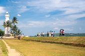 GALLE, SRI LANKA - MARCH 9, 2014: Tourists in front of the oldest Sri Lankan lighthouse placed inside the walls of the ancient Galle fort, a UNESCO world heritage site.