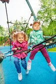 Two funny girls together on grid of playground