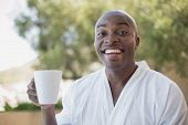 Handsome man in bathrobe having coffee outside on a sunny day