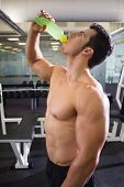 Side view of a shirtless muscular man drinking energy drink in gym