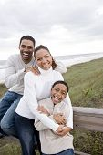 African-American family laughing and hugging at beach