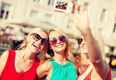 holidays and tourism, modern technology concept - beautiful girls taking picture with digital camera