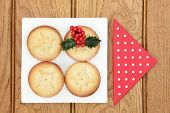 Christmas mince pie cakes on a plate with holly and red serviette over oak background.