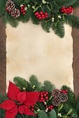 Winter and christmas floral border with poinsettia flower, bauble decorations, mistletoe and winter greenery over parchment paper and oak.