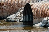 Rusted Culvert Pipe Opening In Water.