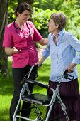 Nurse Walking With A Woman With A Walker