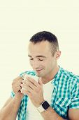Happy Young Man Enjoying Hot Beverage Drinking Coffee From Mug