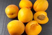 Six Sun Sweet Apricots, One Halved With Stone. Prunus.