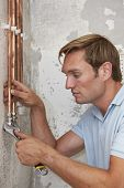 image of pipefitter  - Plumber Fitting Pipes In House On Construction Site - JPG