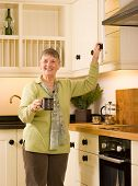 Happy Senior Woman In Designer Kitchen