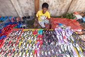 HIKKADUWA, SRI LANKA - FEBRUARY 23, 2014: Young local market vendor selling sandals. The Sunday mark