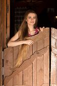 Pretty long hair Cowgirl standing in front saloon entrance