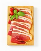 Sliced prosciutto crudo on cutting board