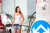 Attractive, young woman refueling her car in a gas station, checking the amount of gas, disliking the price tag and the gas mileage of her engine
