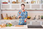 Cheerful young man juggling tomatoes while preparing food in kitchen