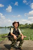 image of shotguns  - Senior hunter with shotgun sitting beside lake - JPG