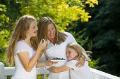Family Of Girls Enjoying A Moment Together While Eating Fresh Fruit Outdoors