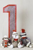 foto of sock-monkey  - Sock monkeys sitting around a wooden number one sign - JPG