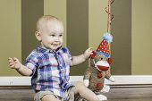 picture of sock-monkey  - An infant boy sitting among balloons and a sock monkey for his birthday - JPG