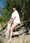 Attractive woman sits on a dry tree on a beach