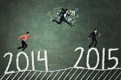 picture of competing  - Three workers compete above number 2014 to 2015 and reach number 2015 symbolizing business competition to get success in the future - JPG