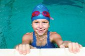 pic of goggles  - beautiful girl in a bathing suit swim cap goggles holding on overboard in a swimming pool - JPG