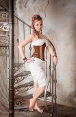 Beautiful Steampunk Woman With Trousers On The Stairway