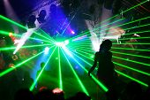 Silhouette of dancing woman between green laser light