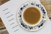 Cup of tea with weekdays listed on white paper