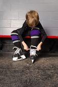 Boy Tying Hockey Skates In Dressing Room