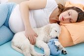 image of golden retriever puppy  - Pregnant woman sleeping with golden retriever puppy at home - JPG