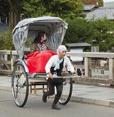 Tourist Riding A Rickshaw In Kyoto, Japan