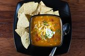 foto of enchiladas  - A bowl of chicken enchilada soup with white corn tortillas on the side - JPG