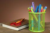 Colorful pens in green metal holder with notebook and scissors on wooden table and shaded color background