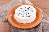 Blue cheese on earthenware dish on burlap cloth and wooden table background