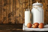 Milk can with eggs, eggshell and glass bottle  on rustic wooden background