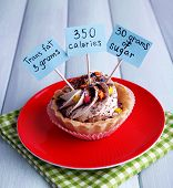 Delicious cake with calories count labels on color plate with napkin, on color wooden table background