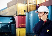 Portrait of a worker in front of a stack of containers