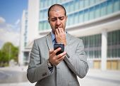 image of dread head  - Portrait of a scared man looking at his mobile phone - JPG