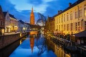 Cityscape With Canal Dijver And A Church Of Our Lady In Bruges At Sunset, Belgium