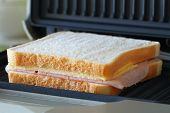 Toast with ham and cheese in toaster, closeup