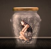 Businesswoman inside a glass jar with lightning drawings concept on background