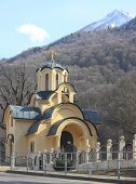pic of olympic mountains  - small church in Krasnaya Polyana against the background of Caucasus mountains - JPG