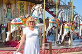 stock photo of carousel horse  - Caucasian happy tourist woman near horse carousel on travel vacation - JPG