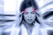 Headache migraine people - Doctor woman stressed. Woman Nurse / doctor with migraine headache overworked and stressed. Health care professional in lab coat wearing stethoscope at hospital.