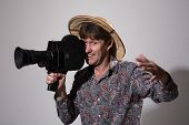 A Man In A Straw Hat With An Old Movie Camera On A Gray Background