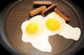 Frying Two Eggs And Sausage In A Pan